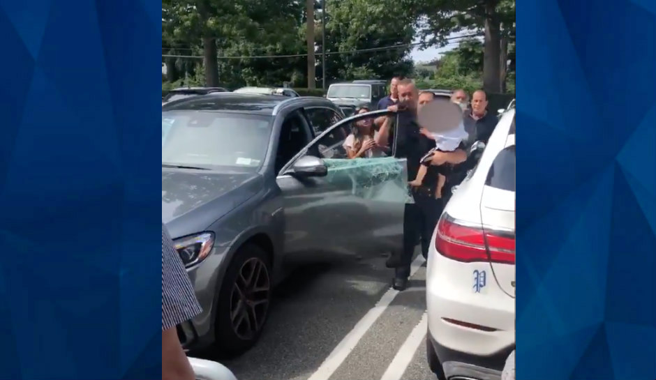police officer carries baby from hot car